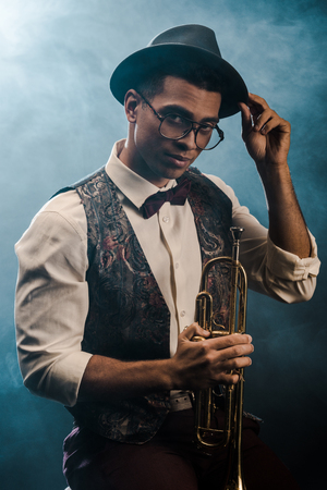 confident stylish young man in hat and eyeglasses posing with trumpet on stage with smoke and dramatic lighting Stock Photo