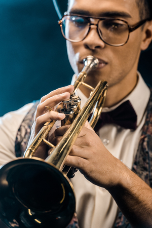 selective focus of young jazzman playing on trumpet on stage with dramatic lighting and smoke