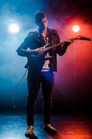 concentrated man in leather jacket performing on electric guitar on stage with smoke and dramatic lighting
