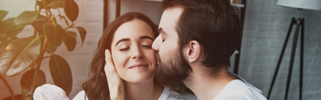 handsome bearded man kissing beautiful smiling woman at home