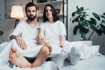 junges Paar im Pyjama, das im Bett liegt und zu Hause in die Kamera schaut