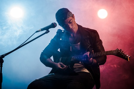 focused male musician playing on electric guitar near microphone on stage during rock concert