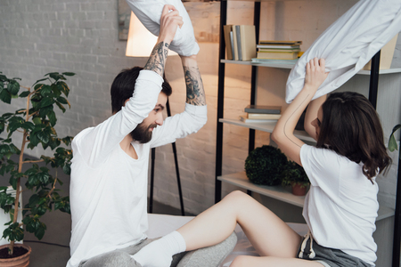 beautiful young couple in pajamas having fun and fighting with pillows at home Stock Photo