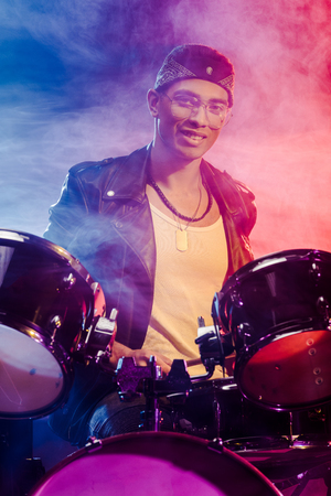 cheerful mixed race male musician sitting behind drum set on stage with smoke and dramatic lighting
