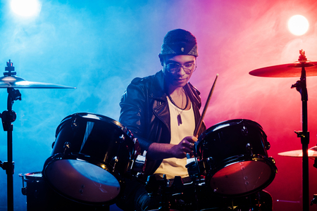 focused young male musician in leather jacket playing drums during rock concert on stage with smoke and spotlights