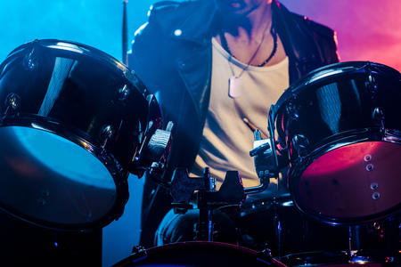cropped shot of male musician playing drums during rock concert on stage with smoke and dramatic lighting