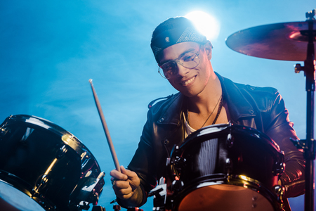 handsome mixed race male musician in leather jacket playing drums during rock concert on stage with smoke and spotlight