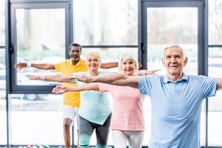 multicultural senior athletes synchronous doing exercise at gym