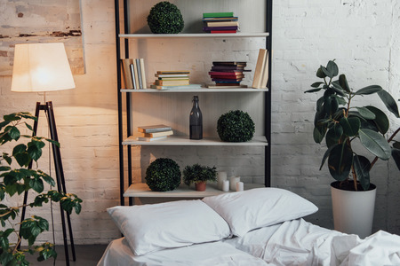 modern interior design of bedroom with rack, plants, lamp, bed and brick wall