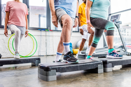cropped shot of senior athletes synchronous exercising on step platforms at gym Stock Photo