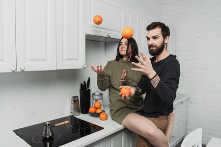 beautiful young couple having fun and juggling with oranges in kitchen Stockfoto