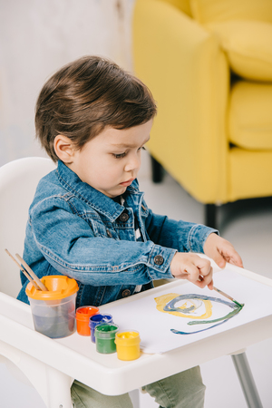 adorable little boy painting with watercolor paints while sitting on highchair Stock Photo - 117396414
