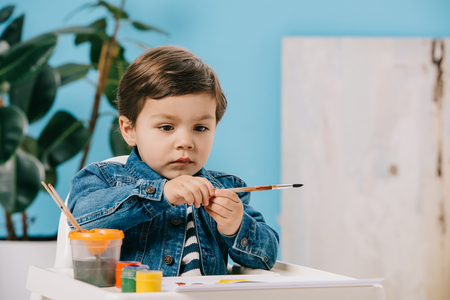 cute little boy holding painting brush while sitting on highchair with watercolor paints on table