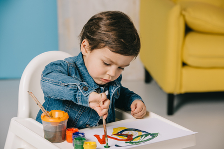 cute little boy painting with watercolor paints while sitting on highchair Stock Photo - 117396422