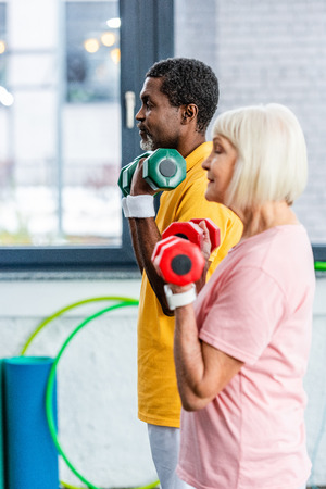 side view of interracial mature couple doing exercise with dumbbells at gym