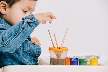 cute little boy choosing painting brush while sitting on highchair with watercolor paints on table isolated on white Stock Photo