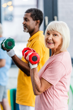 selective focus of senior woman and her african american husband doing exercise with dumbbells at gym Stock Photo
