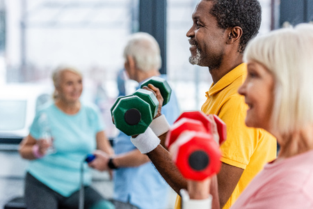 selective focus of interracial mature couple doing exercise with dumbbells at gym Stock Photo - 117396430