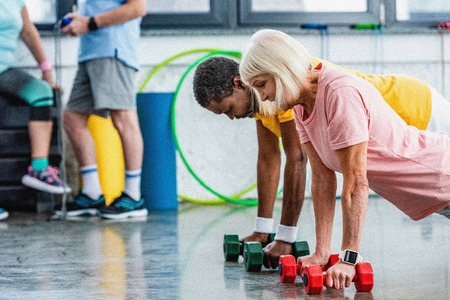 selective focus of interracial couple doing plank with dumbbells at gym