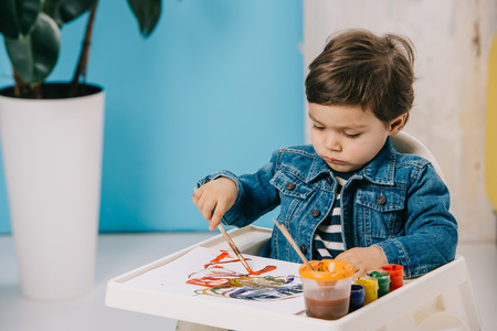 cute little boy painting with watercolor paints while sitting on highchair Stock Photo