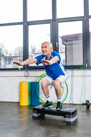 senior sportsman doing squats on step platform at gym