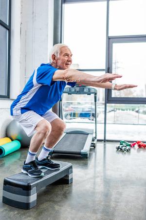side view of senior sportsman doing squats on step platform at gym