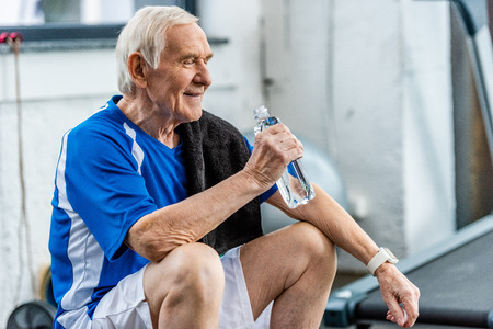 smiling senior sportsman with towel and bottle of water resting at gym Banque d'images