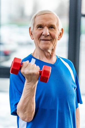 smiling senior sportsman exercising with dumbbell at gym