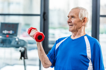 happy senior sportsman exercising with dumbbell at gym Stockfoto