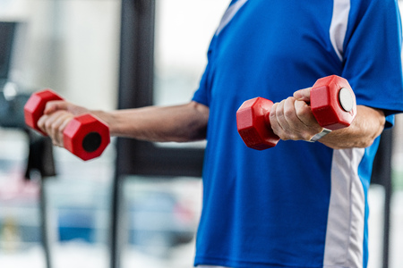 cropped image of senior sportsman exercising with dumbbells at gym