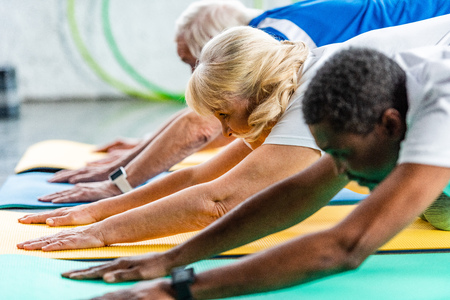 selective focus of senior sportswoman exercising with friends at gym