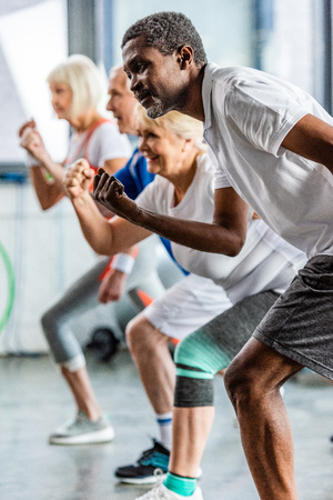 selective focus of african american sportsman synchronous exercising with friends at sports hall