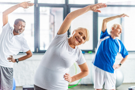 selective focus of smiling senior sportswoman synchronous exercising with male friends at gym