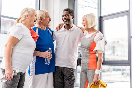 laughing multicultural senior sportspeople talking and embracing each other at gym