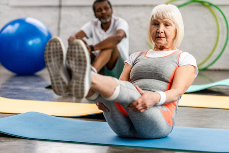 senior woman and her husband exercising on fitness mats at gym