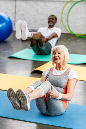 selective focus of senior woman and her husband exercising on fitness mats at gym Stock Photo