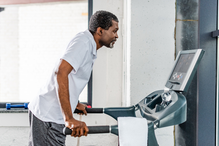 side view of mature african american sportsman running on treadmill at gym Stockfoto