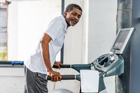 middle aged african american man on treadmill at gym Stockfoto