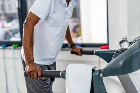 cropped shot of african american man exercising on treadmill at gym