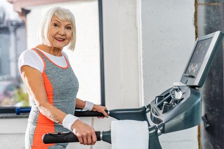 Selektiver Fokus der lächelnden älteren Sportlerin, die auf dem Laufband in der Sporthalle läuft