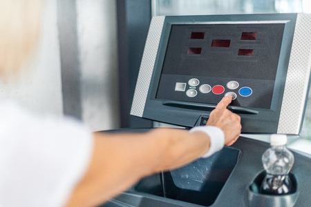 cropped image of sportswoman pushing button on treadmill at gym Stockfoto