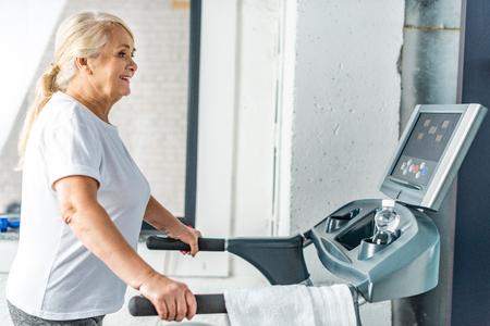 side view of smiling senior sportswoman running on treadmill at sports hall Zdjęcie Seryjne