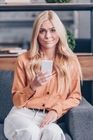 young woman with smartphone frowning and looking at camera indoors