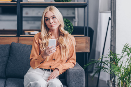 beautiful blonde woman using smartphone and smiling at camera while sitting on couch at home