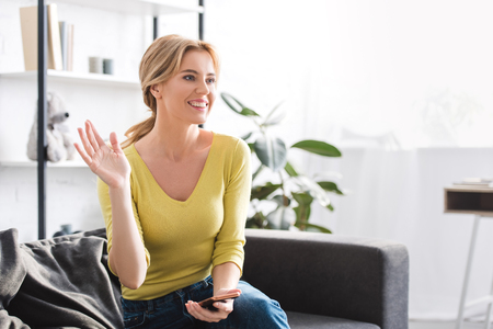 beautiful smiling woman holding smartphone and waving hand while sitting on couch at home