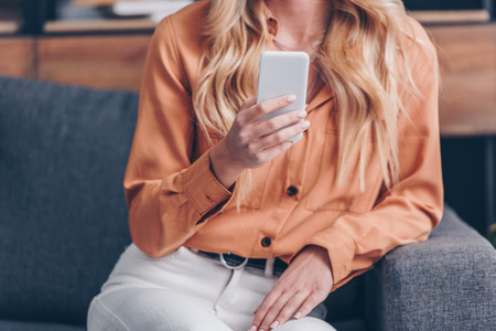 cropped shot of young blonde woman sitting on couch and using smartphone Zdjęcie Seryjne