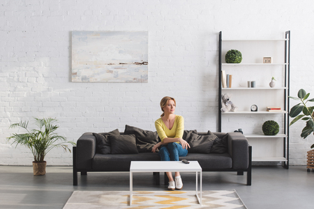 beautiful woman sitting on couch and looking away at home Stock Photo