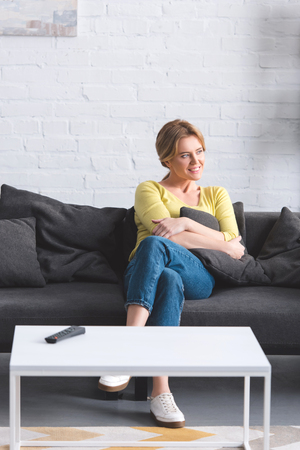 beautiful smiling woman sitting on couch and looking away at home Stok Fotoğraf
