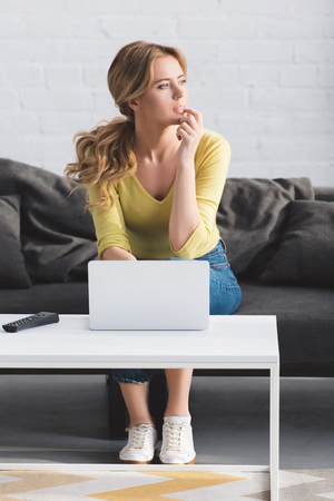 thoughtful woman looking away while sitting on couch and using laptop
