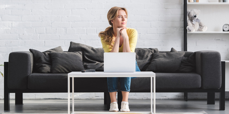 beautiful pensive woman looking away while sitting on couch and using laptop at home